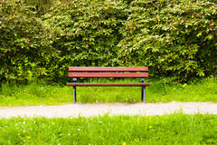 Empty dark red wooden bench in the park Stock Photography