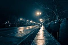 Empty dark and wet urban city street at night. Empty dark and wet urban city street road after rain at night royalty free stock photography