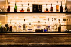 Empty dark wooden bar counter with blur background bottles of re. Staurant, bar or cafeteria background /for your product display royalty free stock photography