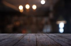 Empty dark wooden table in front of abstract blurred background of cafe and coffee shop interior. can be used for display or stock photos