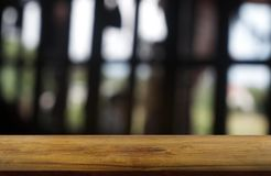 Empty dark wooden table in front of abstract blurred background of restaurant, cafe and coffee shop interior. can be used for stock photo