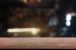 Empty dark wooden table in front of abstract blurred background of restaurant, cafe and coffee shop interior. can be used for royalty free stock photo