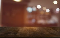 Empty dark wooden table in front of abstract blurred bokeh background of restaurant . can be used for display or montage your stock images