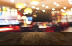 Empty dark wooden table in front of abstract blurred bokeh background of restaurant . can be used for display or montage your stock image