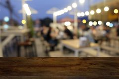 Empty dark wooden table in front of abstract blurred bokeh background of restaurant . stock photo