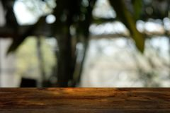 Empty dark wooden table in front of abstract blurred bokeh background of restaurant. stock photography