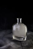 Empty decanter with smoke on black background. Empty glass liquid decanter graceful shape on a black wooden background with smoke in it. Crystal pitcher for Royalty Free Stock Photography