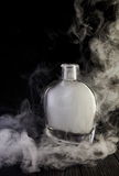 Empty decanter with smoke on black background. Empty glass liquid decanter graceful shape on a black wooden background with smoke in it. Crystal pitcher for Stock Photography