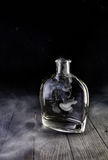 Empty decanter with smoke on black background Stock Photos