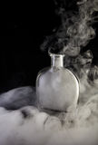 Empty decanter with smoke on black background Royalty Free Stock Images