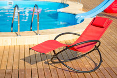 Empty deck-chair near pool. Red empty deck-chair near pool royalty free stock photos
