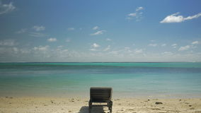 Empty deck-chair on the ocean coast. Vacation scene. Tilt shot of clear blue lagoon skyline and empty chaise-longue on white sand beach. Place in the sun on stock video footage