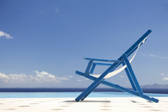 An empty deck chair by a pool Royalty Free Stock Images
