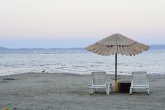 Empty deck chairs and bamboo umbrellas Royalty Free Stock Photos
