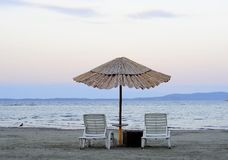 Empty deck chairs and bamboo umbrellas Royalty Free Stock Photo