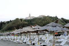 Empty deck chairs and bamboo umbrellas Royalty Free Stock Photography