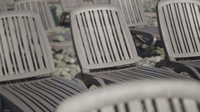 Empty deck chairs on the beach. Pebble Beach. Daylight stock video footage