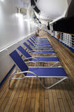 Empty deck chairs on cruise ship. Row of empty identical deck chairs or loungers on wooden  deck of cruise ship at night Royalty Free Stock Photography