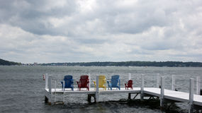 Empty Deck Chairs Signal Summer's End. A row of colorful deck chairs with tiny chair at the end, line an empty pier facing the rolling waters of Lake Geneva,WI Stock Image