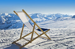 Empty deckchair on the side of a ski slope. Snowy mountain landscape Stock Images
