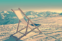 Empty deckchair on the side of a ski slope, vintage. Process Stock Photos