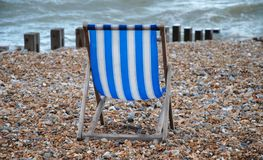 Empty deckchair, St.Leonards. An empty blue and white striped deckchair on the beach at St.Leonards-on-Sea in East Sussex, England Royalty Free Stock Image