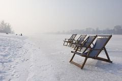 Empty deckchairs on frozen lake Royalty Free Stock Photo