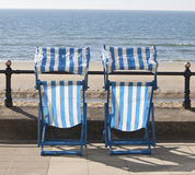 Empty deckchairs looking over the sea stock photos