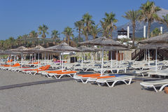 Empty deckchairs with mattresses and towels and umbrellas with a Royalty Free Stock Photo