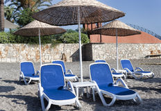 Empty deckchairs and umbrellas with a thatched roof on the beach Royalty Free Stock Photography