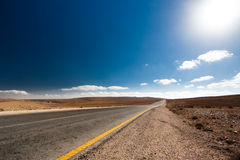 Empty desert road with blue sky. Stock Image