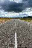 An empty desert road with dark and foreboding storm clouds Royalty Free Stock Photos