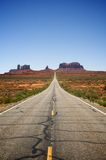 Empty Desert Valley Road. Looking down the center of an empty desert highway running through a valley with rock formations in the background. Vertical shot Royalty Free Stock Image
