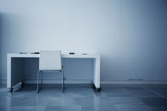 Empty desk. Facing white wall royalty free stock photography