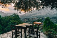 Empty dining table with chairs overlooking mountains with low hanging clouds and green olive trees. South Crete neat royalty free stock images