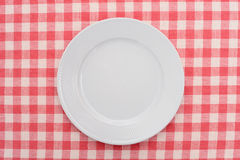 Empty dinner plate. On red and white checked gingham tablecloth Royalty Free Stock Photo