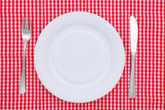 Empty dinner plate. With fork and knife on red and white checked gingham tablecloth Stock Photos