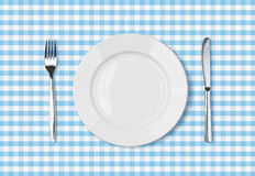 Empty dinner plate top view on blue picnic table cloth Stock Image