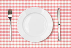 Empty dinner plate top view on pink picnic tablecloth. Empty dinner plate top view on pink picnic table cloth Royalty Free Stock Photography
