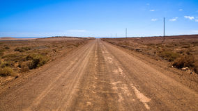 Empty dirt road. Empty and dusty dirt road, leading to infinity Royalty Free Stock Image