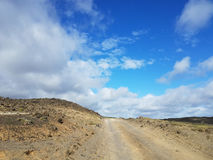 Empty dirt road next to lava field Stock Image