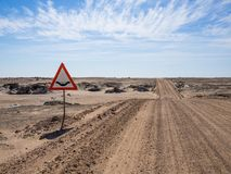 Empty dirt road and water crossing sign in Namib desert of Namib-Naukluft National Park, Namibia, Africa stock photos