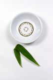Empty dish. Full view of a empty dish with bamboo leaf on the white backgound Royalty Free Stock Photo