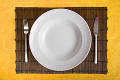 Empty dish on bamboo board Royalty Free Stock Photo