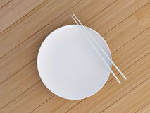 Empty dish with chinese sticks. Round white plate, knife and fork on wooden table Royalty Free Stock Photography