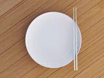 Empty dish with chinese sticks. Round white plate, knife and fork on wooden table Stock Photography
