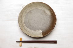Empty dish with chopsticks Stock Image