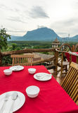 Empty dish with fork and spoon on red table cloth and look at mountain view Stock Images