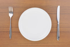 Empty dish, knife and fork. Empty white dish, knife and fork on wood table stock image