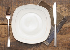 Empty dish, knife and fork and brown napkin Stock Images